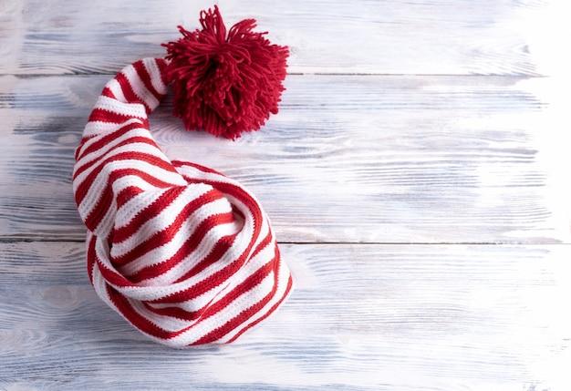 Un bonnet rayé rouge et blanc avec une longue queue et un grand pompon rouge est sur une table en bois blanc, plat, vue de dessus.