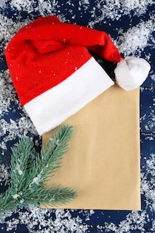 Bonnet rouge avec branche de sapin, feuille de papier et flocons de neige sur fond de bois de couleur