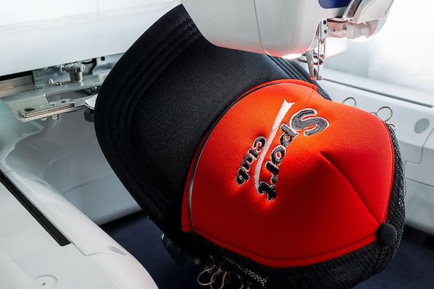 Bonnet de sport brodé et machine à broder en gros plan, image