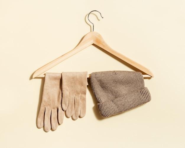 Bonnet tricoté beige et gants en daim sur cintre avec fond de couleur beige