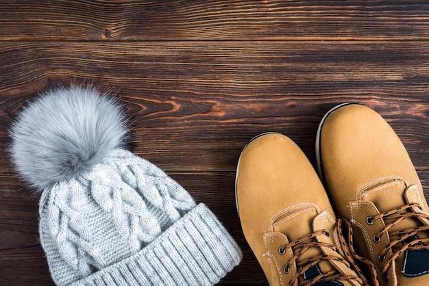 Bonnet tricoté gris hiver avec boom et bottes jaunes sur bois.
