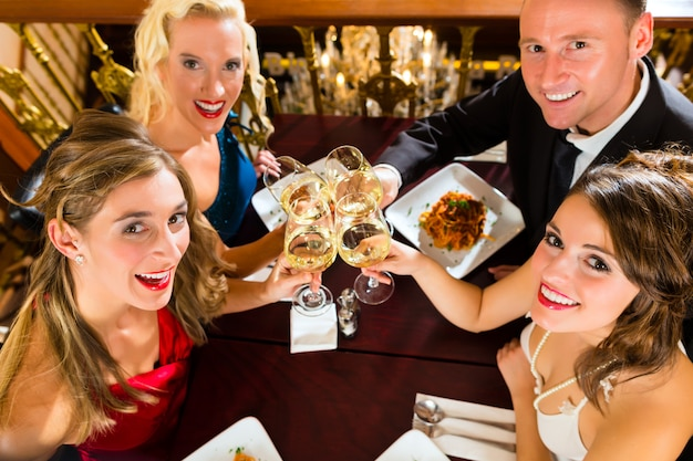 Bons amis pour le dîner ou le déjeuner dans un bon restaurant, cliquetis