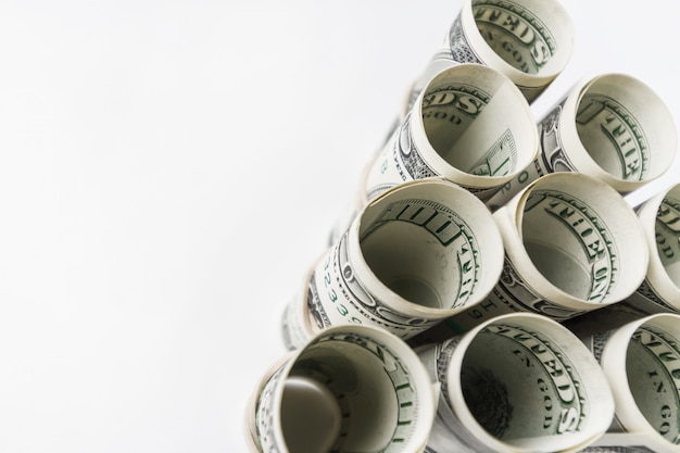 Bons de cent dollars américains roulés et empilés dans une pyramide.