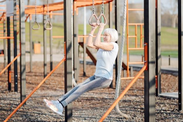 Bons exercices. femme blonde sérieuse faisant des tractions tout en faisant de l'exercice en plein air