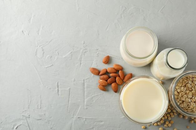 Bootle et verre de différents types de lait sur gris
