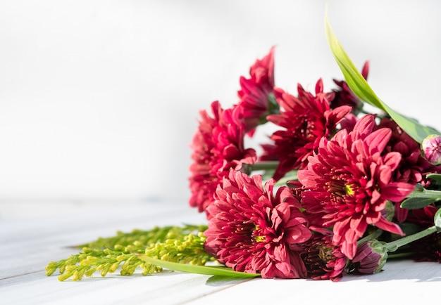 Boquet de belles fleurs de chrysanthème fraîches rouges sur un fond en bois blanc