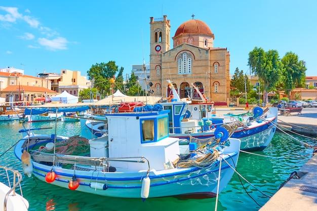 Bord de l'eau avec l'église ekklisia isodia theotokou dans la ville d'égine et vieux bateaux de pêche amarrés, l'île d'égine, grèce