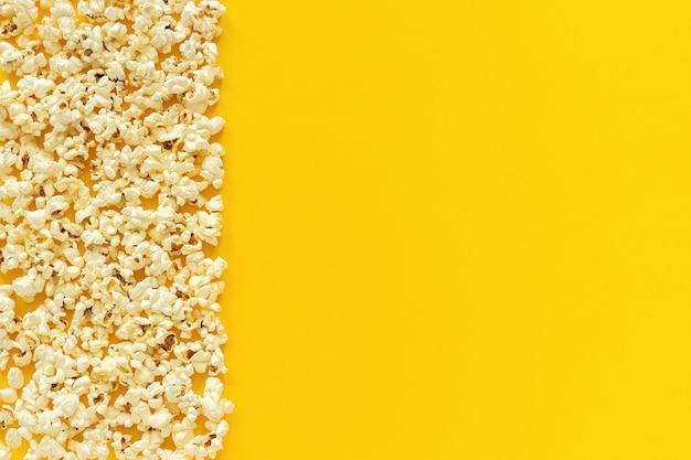 Bord gauche de maïs soufflé épars et espace vide sur fond de papier jaune.