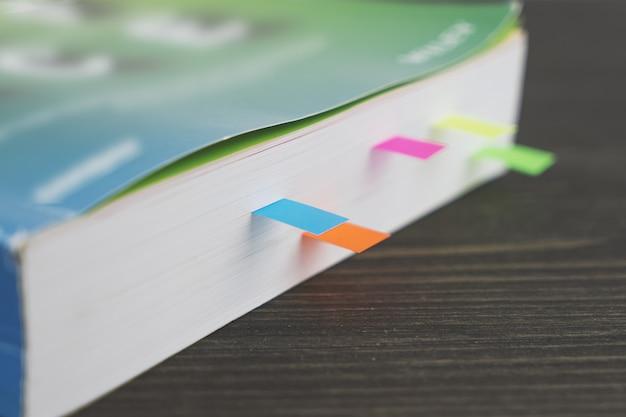Bord d'un livre épais avec des signets colorés sur une table en bois
