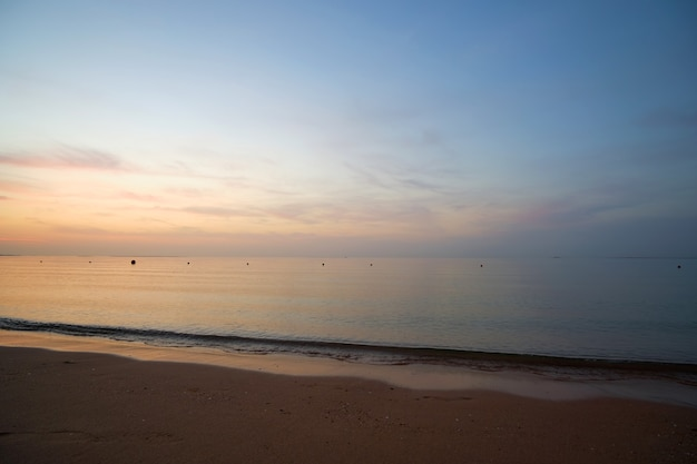 Bord de mer calme avec des vagues écrasantes sur la plage de sable au lever du soleil.