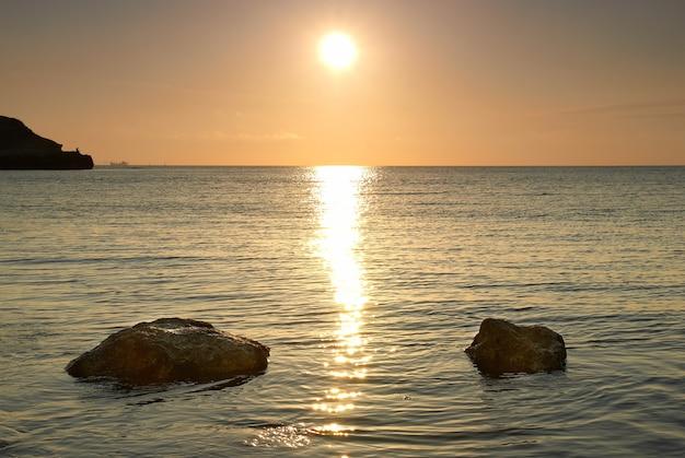 Bord de mer et paysage marin de pierres au coucher du soleil