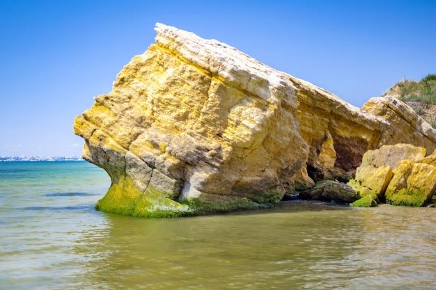 Bord de mer toujours avec de l'eau bleue et des pierres. pierres d'algues moussues sur une plage volcanique.