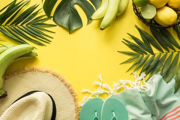 Bordure d'accessoires féminins de plage de tenue. vacances tropicales, chapeau de soleil en paille, serviette, feuilles de monstera sur jaune. concept d'été.