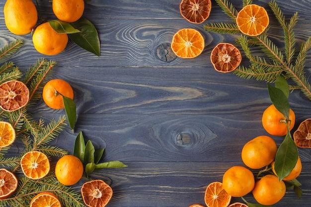 Bordure, cadre de branches de sapin de noël, tranche de fruits orange séchée sur le vieux fond de table de bureau en bois.