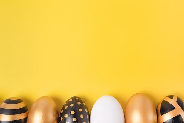 Bordure de cadre d'oeufs de pâques d'or sur jaune