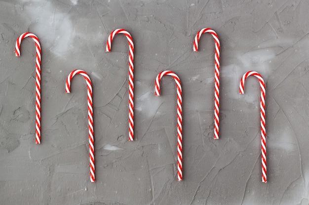 Bordure de cannes de bonbon rouges et blanches sur fond gris. concert des fêtes de noël