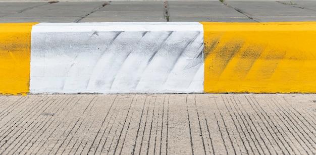 Bordure de couleur jaune et blanche tachée de pneus.