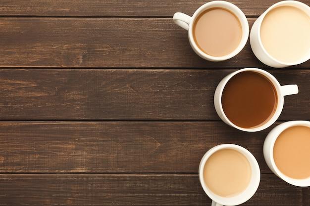 Bordure de divers types de café dans des tasses de différentes tailles sur une table en bois rustique, vue de dessus, espace pour copie