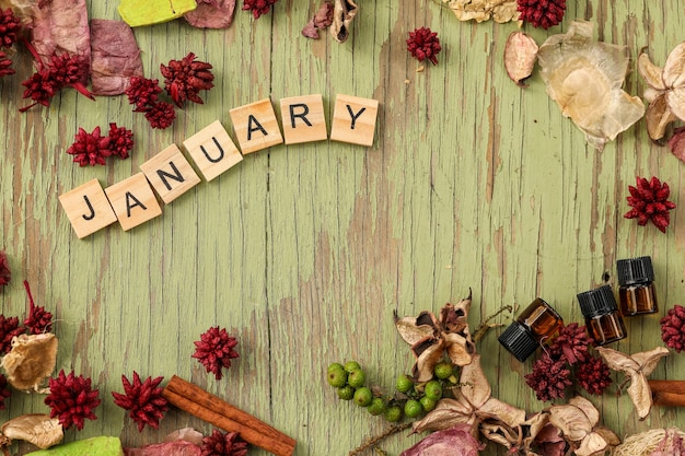 Bordure de diverses fleurs séchées entourant des lettres en bois épelant le mot janvier