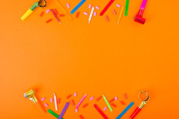 Bordure faite avec des bougies, des bonbons, soufflant corne et bâton de crème glacée sur un fond orange