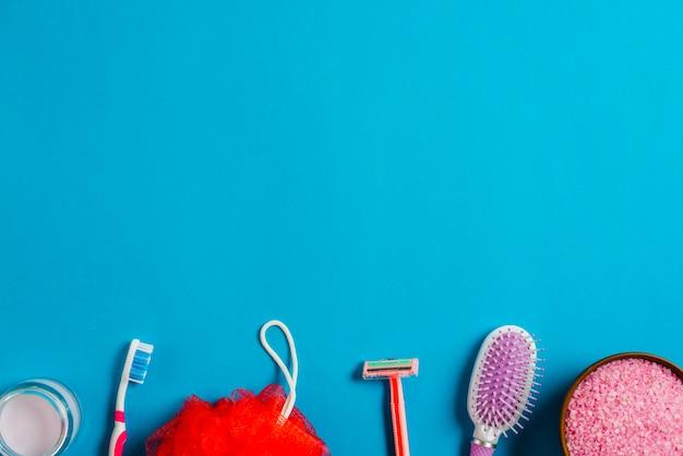 Bordure inférieure faite avec une brosse à cheveux; crème; brosse à dents; le rasoir; bouffée de bain et sel sur fond bleu