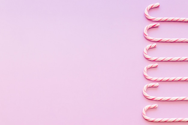 Bordure latérale faite avec des bonbons de canne de noël sur fond rose