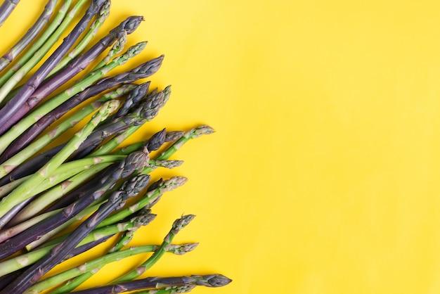 Bordure de légumes à partir de lances d'asperges crues naturelles fraîches pour la cuisson des aliments diététiques faits maison sur fond jaune.