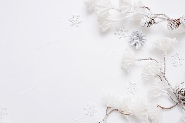 Bordure de noël blanche avec des cônes, des flocons de neige et des fleurs enneigées
