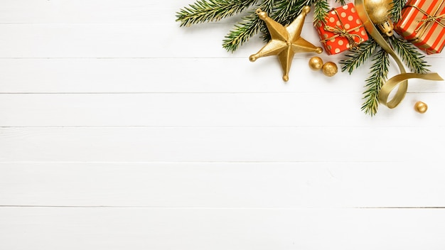 Bordure de noël faite de branches de sapin coffrets cadeaux en or rouge ruban d'or boules faites à la main sur fond de bois blanc. directement au-dessus, copiez l'espace