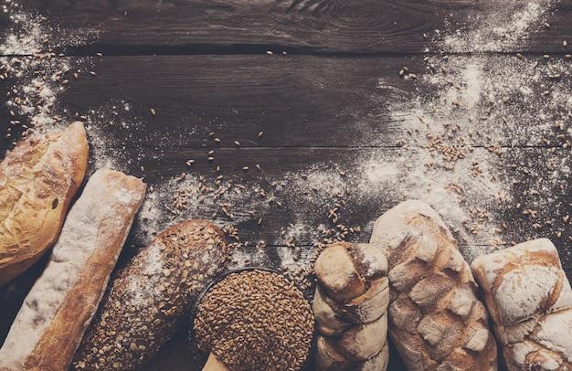 Bordure de pain sur fond en bois foncé. composition de nature morte de pains de grains entiers bruns et blancs avec de la farine de blé saupoudrée autour. concept de boulangerie, cuisine et épicerie.