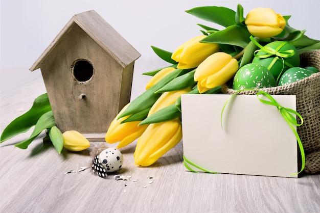 Bordure de pâques avec des tulipes jaunes et des décorations naturelles