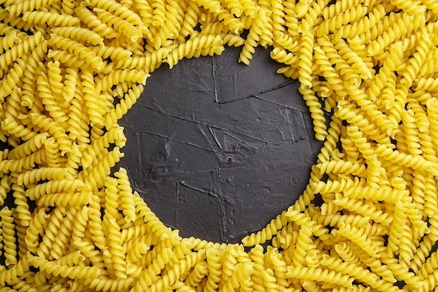 Bordure de pâtes italiennes girandole sur la vue de dessus de table en pierre noire