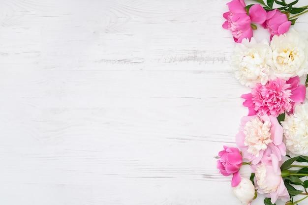 Bordure de pivoines blanches et roses sur fond en bois blanc. copiez l'espace, vue de dessus.