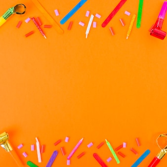 Bordure supérieure et inférieure ornée de bougies, de cornes soufflantes et d'objets décoratifs sur fond orange