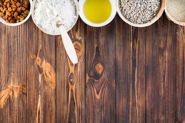Bordure supérieure d'ingrédients de pain dans le bol sur fond en bois