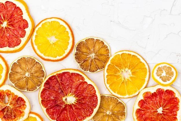 Bordure de tranches séchées de divers agrumes sur fond blanc. beaucoup de pamplemousse citron orange avec fond