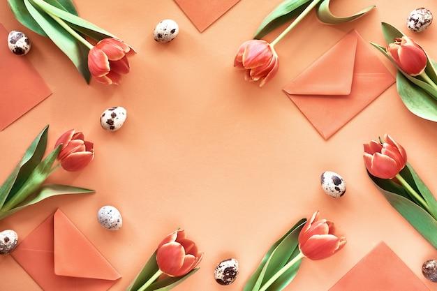 Bordure en tulipes printanières, œufs de caille, cartes de vœux et enveloppes avec nid d'oiseau au milieu.