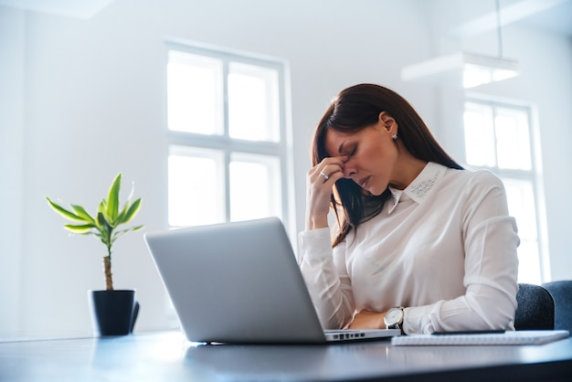 Bored jeune femme au bureau avec un ordinateur portable