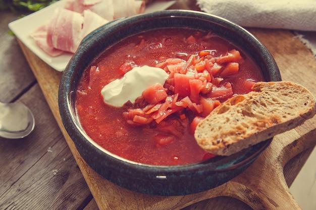 Borsch national soupe rouge ukrainienne et russe. soupe de betteraves rouges sur fond en bois
