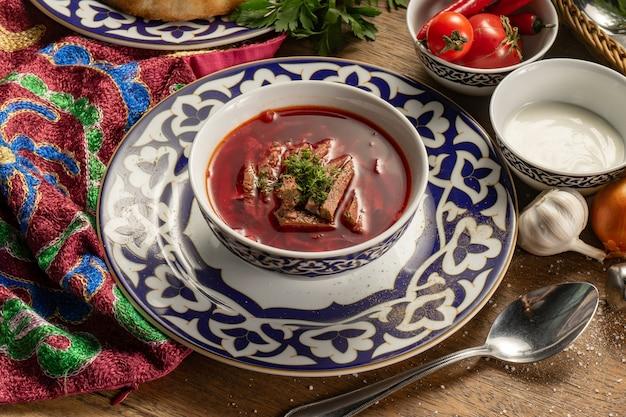 Bortsch à la crème sure. soupe ukrainienne traditionnelle de bœuf, de betterave, de chou et d'herbes dans une assiette avec un motif national ouzbek