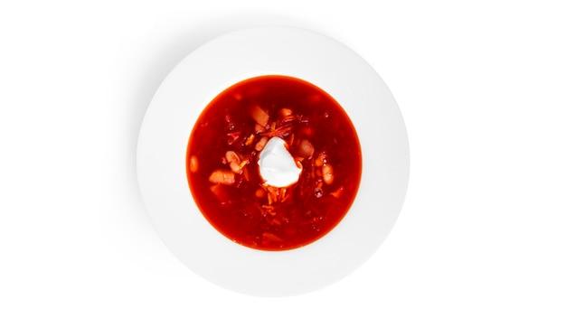 Bortsch rouge et chaud - soupe de betteraves à la crème sure isolé sur blanc.