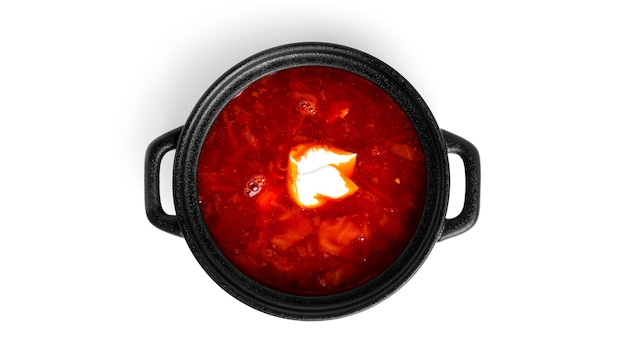 Bortsch rouge et chaud - soupe de betteraves à la crème sure en pot noir isolé sur blanc.