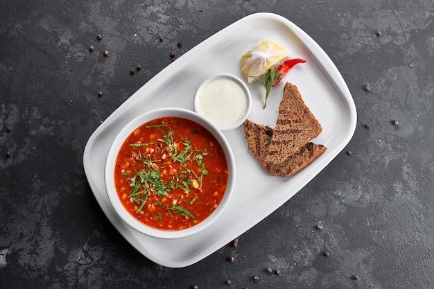 Bortsch rouge sur une plaque blanche avec du pain et de la crème sure