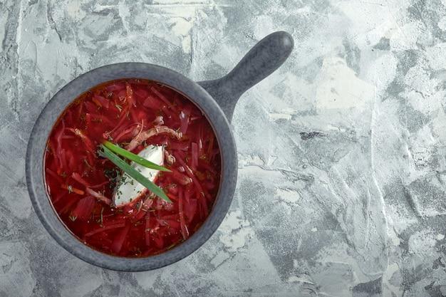 Bortsch russe ukrainien traditionnel avec de la crème sure sur un bol. assiette de soupe de betterave rouge bortsch sur un marbre gris. cuisine ukrainienne traditionnelle