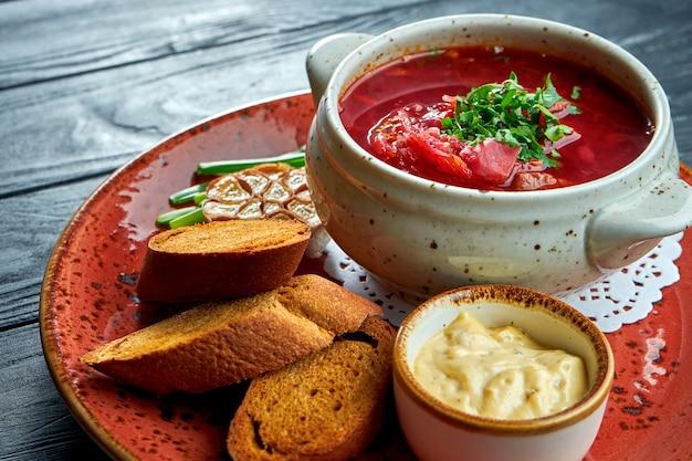 Bortsch ukrainien traditionnel avec côtes et crème sure, servi dans une assiette rouge avec pain de seigle et beurre aromatique sur table en bois