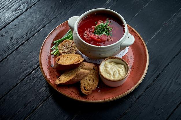 Bortsch ukrainien traditionnel avec côtes levées et crème sure, servi dans une assiette rouge avec pain de seigle et beurre aromatique sur fond sombre. soupe rouge