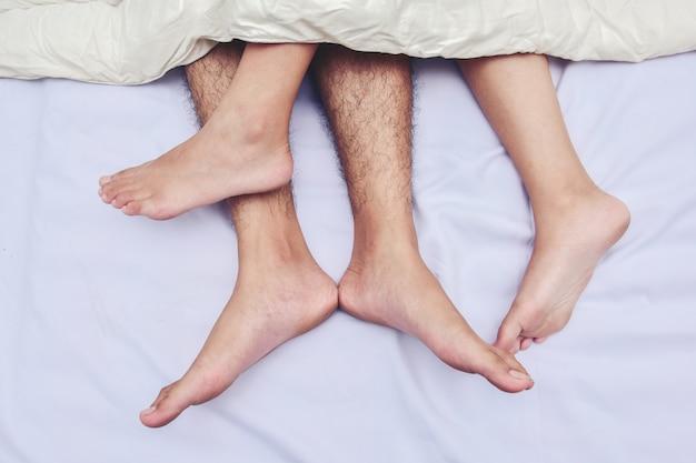 Bosses quelques pieds dans le lit. amour, sexe et partenaires.