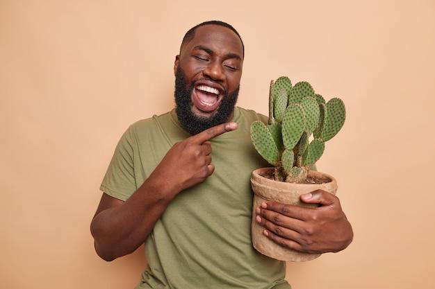 Le botaniste positif d'homme barbu drôle avec la peau foncée pointe au pot de cactus succulent