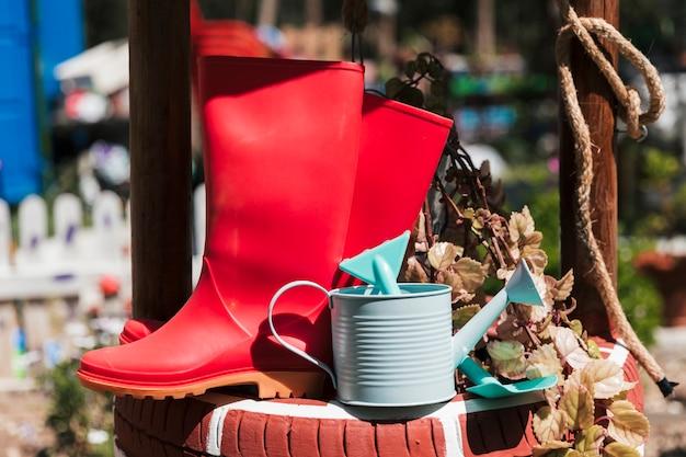 Botte en caoutchouc rouge; arrosoir et bêche près de la plante en pot