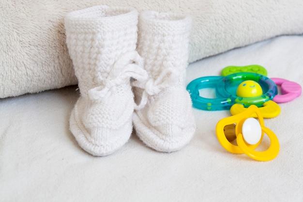 Bottes et accessoires tricotés bébé sur une surface blanche